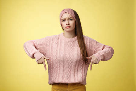 Why me, gosh. Gloomy upset complaining cute glamout young european girl in casual sweater, headband frowning, whining grimacing displeased pointing down, unhappy see lots work over yellow wall