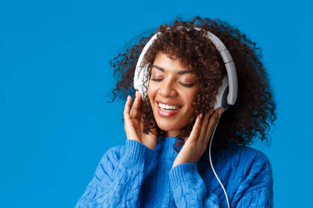 Close-up portrait tender and carefree happy smiling, sensual african-american woman in big headphones, close eyes and grinning romantic recall nice memories from listening song, blue background