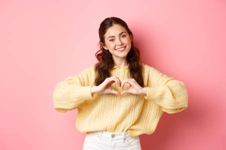 Beautiful romantic girl say I love you, showing heart sign and smiling at camera, standing cute against pink background