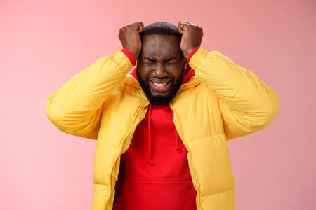 Depressed heartbroken black bearded boyfriend go crazy pissed squeez head frowning squinting clenching teeth painful feeling inside standing devastated distressed pink background suffering headache