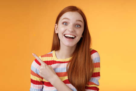 Amused carefree thrilled emotional redhead female fan adore talking favorite movie pointing upper left corner fascinated smiling broadly happy delighted attend incredible party, orange background