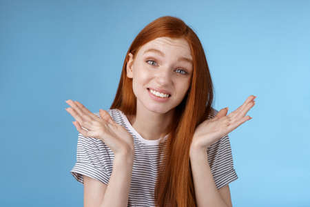 Awkward apologizing cute redhead girlfriend say sorry shrugging spread hands sideways puzzled smiling uncomfortably standing clueless unaware forgetting meeting, posing blue background