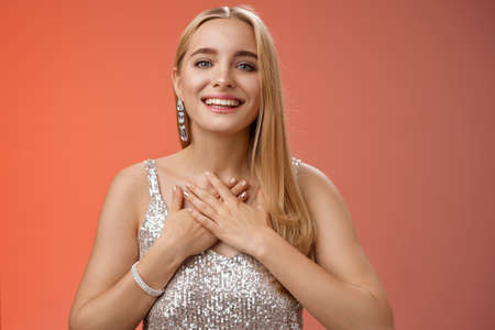 Grateful charming blond european 25s woman in silver party dress press palms heart feel thankful appreciate effort cherish romantic gesture receive flattering compliments gifts, smiling happily