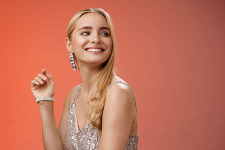 Elegant glamour gorgeous young rich blond woman attend charity party in stylish silver glittering dress accessorize turning right smiling greeting familiar person grinning joyfully, red background