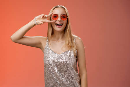 Energized friendly good-looking blond 25s woman in silver stylish dress sunglasses show peace victory gesture carefree smiling camera have fun enjoying cool party, standing red background