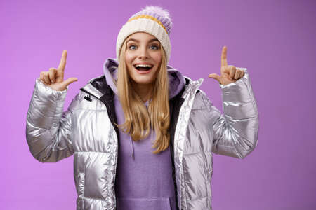 Excited carefree cheerful fair-haired european girl in silver jacket winter hat raising hands pointing up have excellent idea smiling broadly speaking passionately standing purple background