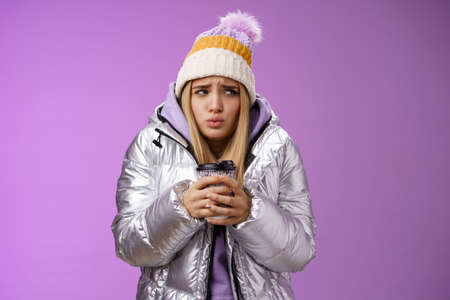 Trembling uncomfortable cute pouting young blond girl feel freezing cold winter snowy weather outside shaking low temperature hold take-away hot coffee cup warming up, purple background