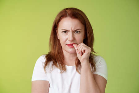 Confused puzzled redhead middle-aged mother perplexed look troubled solving troublesome situation pondering solution biting thumb nail frowning intense stare camera thinking thoughtfully