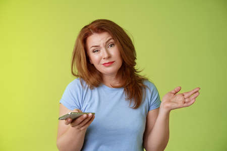 Well meh. Indifferent careless hesitant redhead middle-aged woman mature red female shrugging hold smartphone smirk bored uninterested hold hand aside apathetic attitude green background