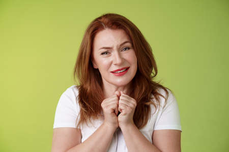 Silly touched tender redhead charmed middle-aged woman sighing gladly gaze admiration delighted press hands together heartwarmed fascinated look grateful lovely camera green background