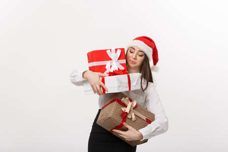 Business Concept - Beautiful young caucasian business woman with santa hat holding too much christmas gift boxes with worry face.