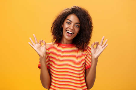 Waist-up shot of chill outgoing calm girlfriend with confident look in trendy striped t-shirt showing okay or excellent gestur and smiling broadly assuring everything alright over orange background