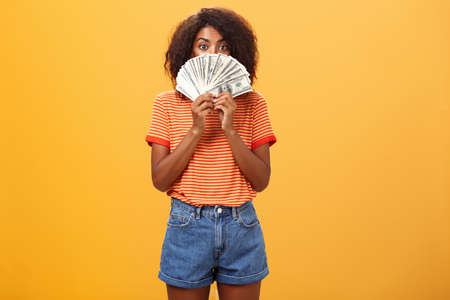 Woman gonna waste lots of cash today. Pleased and delighted rich african american girl with curly hairstyle hiding face behind bunch of money peeking mysteriously at camera winning millions Stock fotó