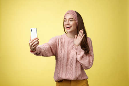 Charming outgoing girlfriend having online video chat, holding smartphone waving at phone camera saying hello talking via videocall smiling friendly during pleasant conversation, recording greeting Foto de archivo