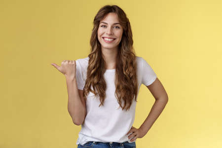 Friendly outgoing cheerful european cute female giving tips showing direction lively smiling toothy happily have nice pleasant conversation pointing left thumb introduce promo yellow background