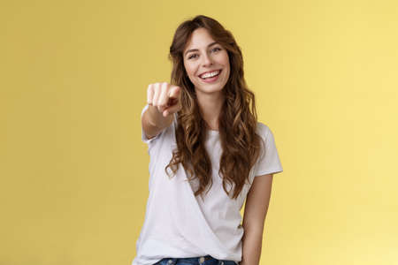 We need you. Cheerful outgoing cute caucasian enthusiastic girlfriend pointing camera asking join her team tilt head smiling broadly congratulate friend great effort stand yellow background