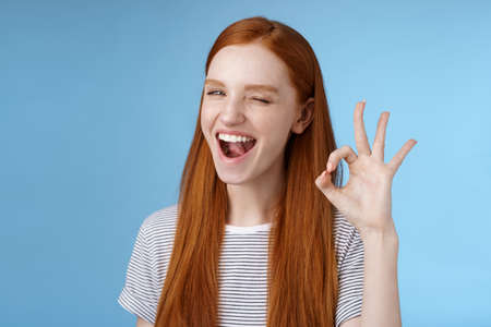 Sassy attractive redhead girl winking mysteriously smiling broadly give approval sign show okay ok excellent gesture satisfied good choice agree great decision, standing delighted blue background Stock fotó