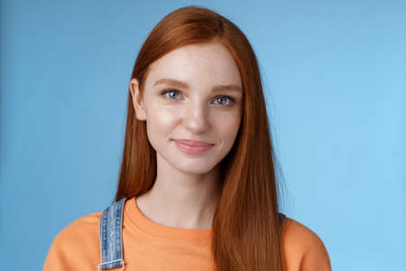 Outgoing young redhead girl blue eyes wearing orange t-shirt overalls smiling pleasantly casually talking standing good mood joyful emotions blue background, listening interesting conversation