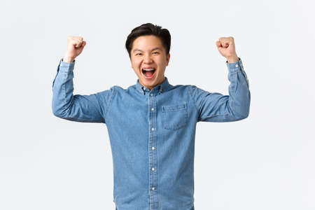 Excited happy asian man with braces feeling success over winning prize, fist pump and shouting yes, rejoicing, triumphing as becoming champion, standing white background celebrating