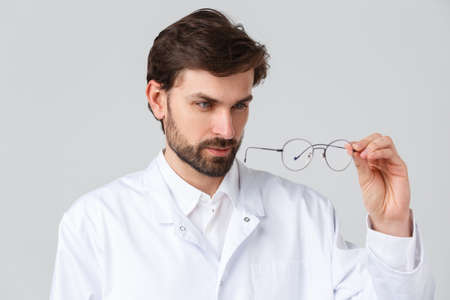 Hospital, healthcare workers, covid-19 treatment concept. Close-up handsome bearded doctor in scrubs, looking closely to glasses lense, picking appropriate lense for eyewear, grey background