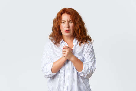 Portrait of sad and concerned middle-aged redhead woman express compassion, pity and disappointment, frowning and gasping upset, clasp hands together, feeling worried Banque d'images
