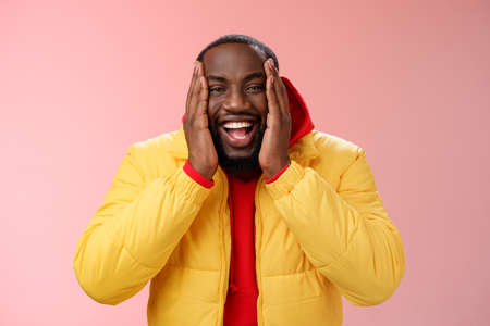 Happy charismatic playful african american bearded guy in yellow jacket red hoodie press palms cheeks smiling friendly laughing happily joking cannot believe receive awesome surprise, winning lottery