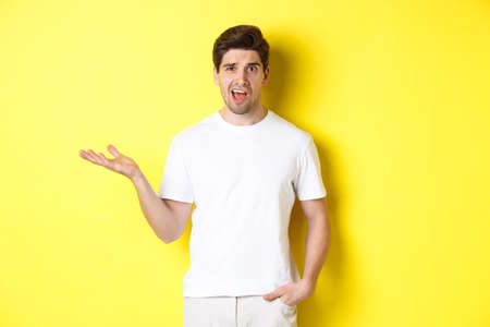 Confused and shocked man complaining, raising one hand and looking bothered, standing near yellow copy space