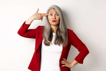 Annoyed and sarcastic asian female entrepreneur shooting herself with finger gun, staring bothered at camera, standing against white background