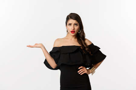 Fashion and beauty. Annoyed woman in black dress raising hand, so what gesture, looking confused at camera, standing bothered over white background