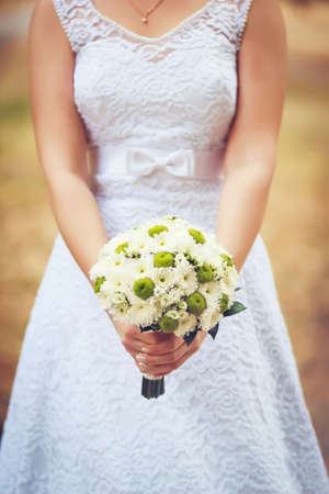 marguerites: Bride holding bouquet of marguerites in her hands in a Wedding Day with blurry background