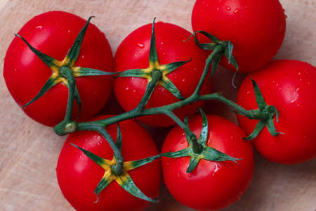 fleshy: Branch of fleshy tomatoes on a wooden table closeup Stock Photo
