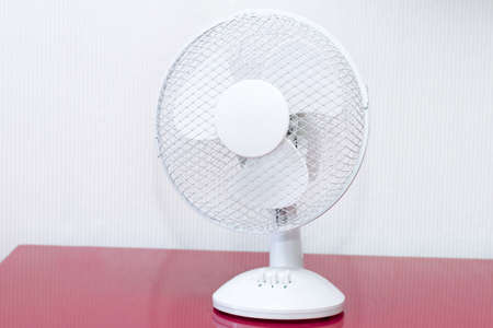 moveable: White table ventilator with spinning blades closeup