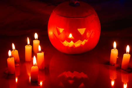 sneer: Scary Halloween pumpkin lantern (jack-o-lantern) with burning candles on a dark wooden background