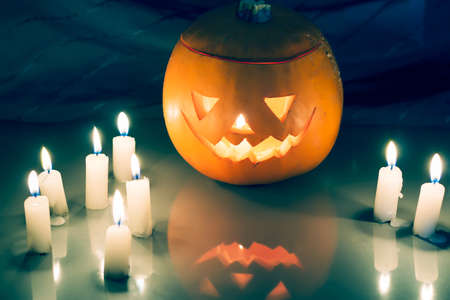 pit fall: Scary Halloween pumpkin lantern (jack-o-lantern) with burning candles on a dark wooden background