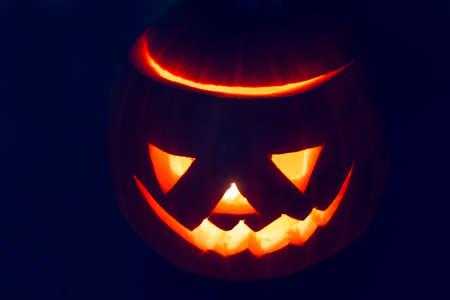 snoot: Scary Halloween pumpkin lantern (jack-o-lantern) with burning candle inside Stock Photo
