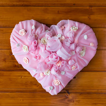 saint valentine   s day: Pink Textile chiffon Heart with roses and other flowers on a wooden background.