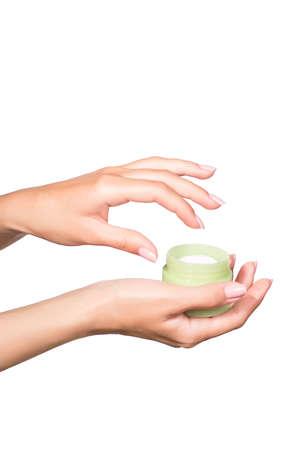manicured hands: Female manicured hands holding cream jar isolated on white background