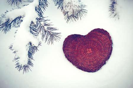 saint valentine   s day: A rattan heart on snow background under pine tree branch, vintage effect