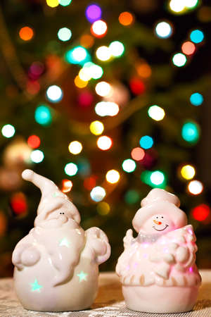 jack frost: Illuminated Snowman and Jack Frost (Santa Claus) dolls in front of Christmas tree lights that are defocused, blurred background