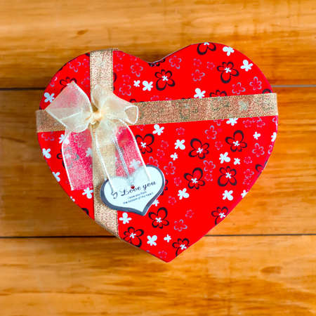 saint valentine   s day: Gift box with heart shape with inscription i love you on wooden background