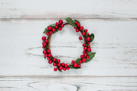 red berries: Christmas wreath decorated with red berries on a white wooden background