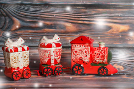 christmas toy: Toy red christmas train on a dark wooden background, snow falling