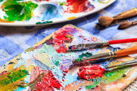 Colourful oil paint, different types of brushes and palette Stock Photo