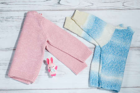 warm things: Pair of sweaters for babies on a rustic white background Stock Photo