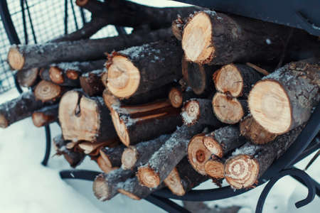 chock: Chopped firewood on a stack in snow, winter, selective focus
