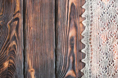 wooden surface: Delicate crocheted handmade woolen downy material over rustic brown wooden background