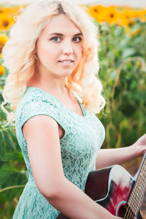 field mint: Portrait of a beautiful smiling blonde girl in a straw hat outdoors with guitar