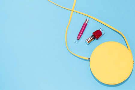 Round yellow purse, red nail polish, red lipstick on a pastel blue background. Summer collection of female accessories Stock Photo