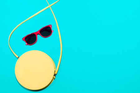 Round yellow bag and red glasses on blue background, top view, copy space