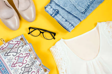 Silk white top, denim shorts, nude shoes, purse, black eyeglasses on a bright background